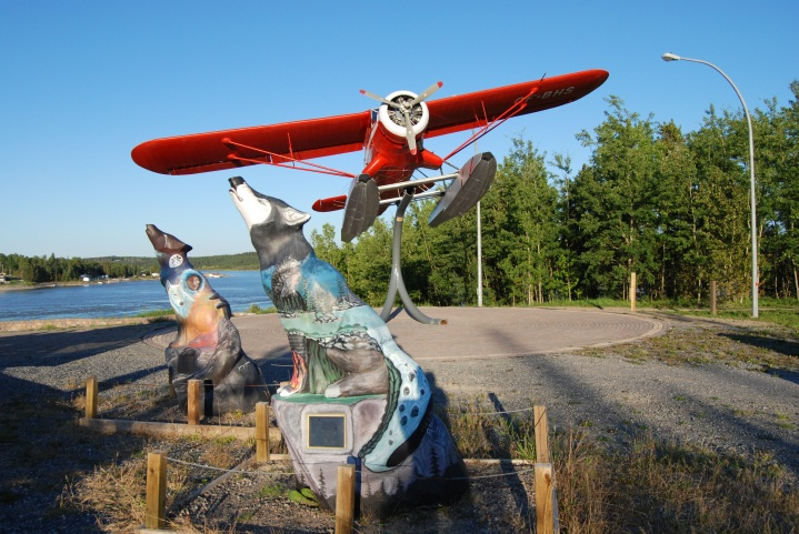 Two wolf statues overlook the Burntwood River at the northern end     of Spirit Way. The rebuilt Norseman floatplane appears to be taking off from the floatplane base behind it.