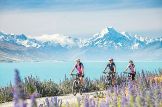 Cycling along scenic Lake Pukaki on the Canterbury Plains with Mt. Cook in the background.