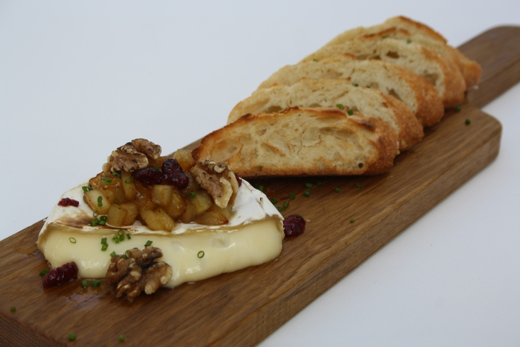 Baked brie served alongside a crusty baguette.