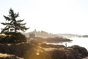 A solitary lighthouse stands on the rocky shoreline.