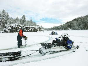 Researcher Ken Sandilands drilling through the ice to sample a lake in the winter.