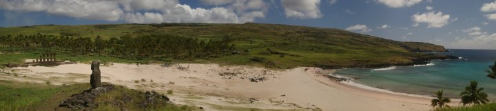 A panoramic view of Anakena beach showing an ahu in the background featuring numerous moai.